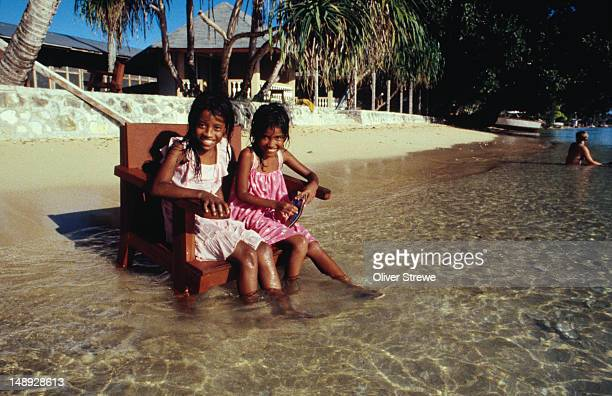 A pair of girls sitting on a chair in the shallow waters.