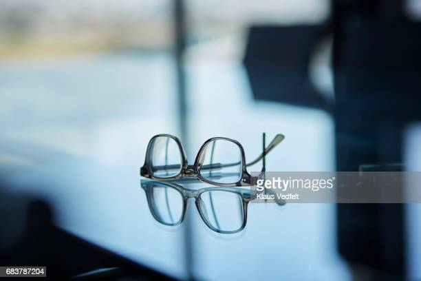 Pair of glasses on glass table