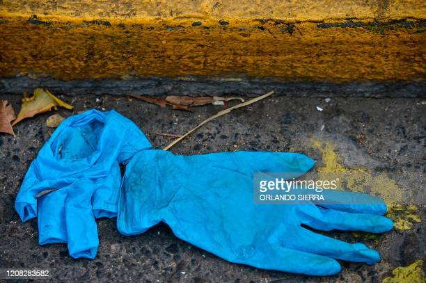 Pair of gloves lie on the floor, after been used to prevent the spread of the new coronavirus, COVID-19, in Tegucigalpa, on March 26, 2020. - The...
