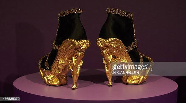 A pair of gold shoes created by British designer Alexander McQueen sit on display during a photocall for an exhibition entitled 'Shoes Pleasure and...