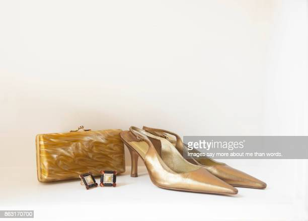 Pair of golden shoes, golden clutch and earrings.