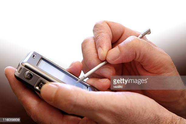 pair of hands holding a pda and stylus - elektronische organiser stockfoto's en -beelden