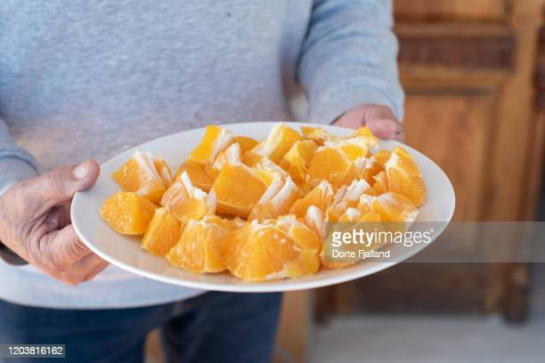 a pair of hands holding a white plate with a peeled and sliced, fresh orange - dorte fjalland stock pictures, royalty-free photos & images