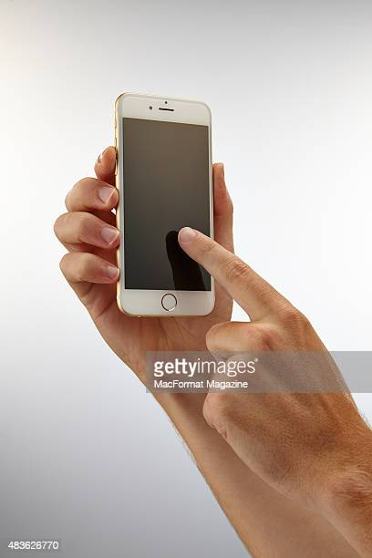 A pair of hands holding and using the touchscreen of an Apple iPhone 6 taken on September 24 2014