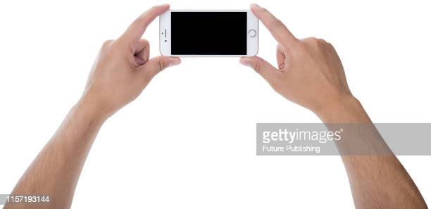 A pair of hands holding up a 2016 Apple iPhone 7 smartphone with a Rose Gold finish taken on September 22 2016