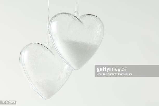 Pair of heart-shaped glass ornaments partially filled with snow