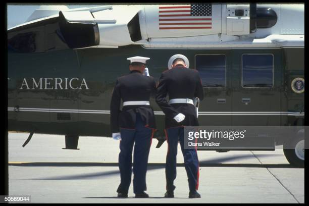 Pair of honor guardtypes bowing in homage in front of Pres Bush's copter during 1st Couple's appearance at Air Force Academy graduation
