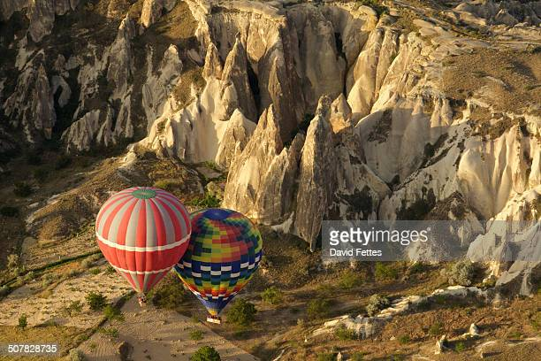 Pair of hot air balloons floating next to each other in valley, Cappadocia, Anatolia, Turkey