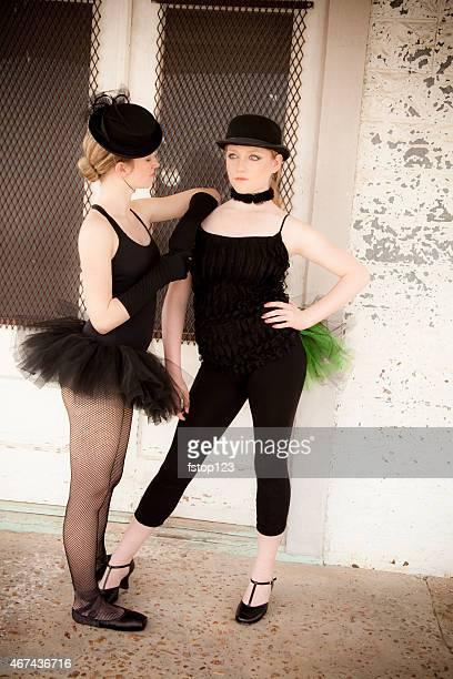 Pair of jazz ballet dancers wearing costume pose for camera.