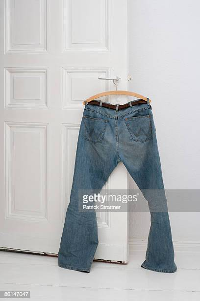 A pair of jeans hanging on a door handle