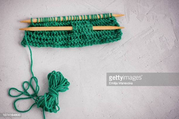 A pair of knitting needles, knitting and a ball of yarn
