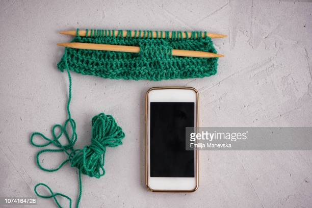 A pair of knitting needles, knitting and cell phone