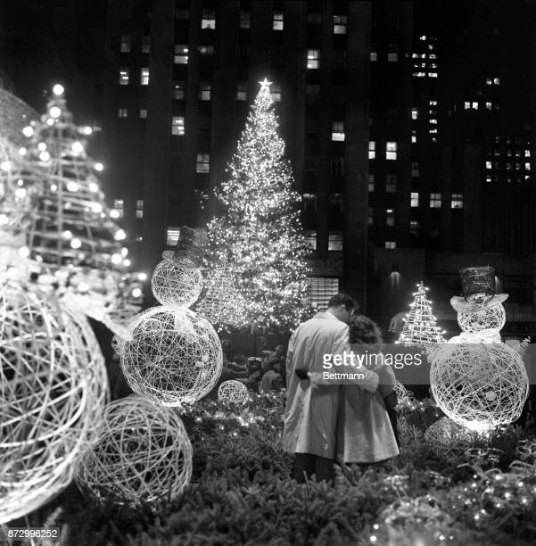 A pair of lovers are entranced by the beauty of the scene after the traditional Rockefeller Center Christmas tree was lighted The couple is framed by...