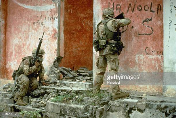 A pair of Marines from Task Force Mogadishu prepare to clear a building during a raid on a weapons cache as part of the multinational relief effort...