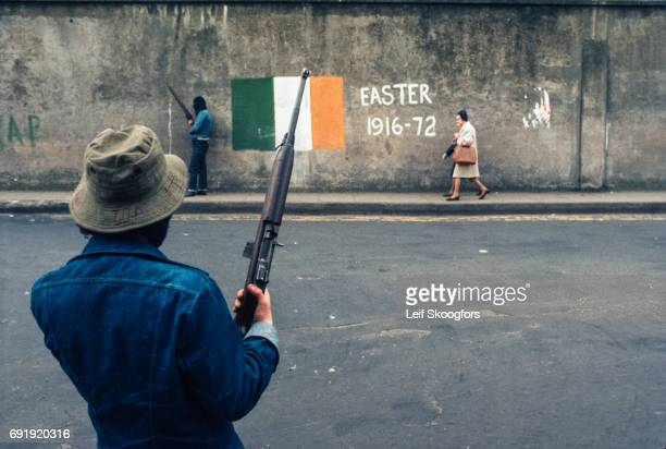 A pair of masked members of the Provisional Irish Republican Army both armed guard a checkpoint at an intersection in the Catholic Bogside...