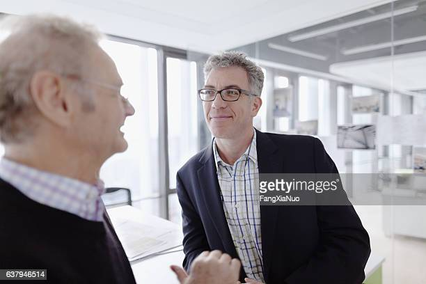 pair of mature men talking together in design agency - old university stock pictures, royalty-free photos & images