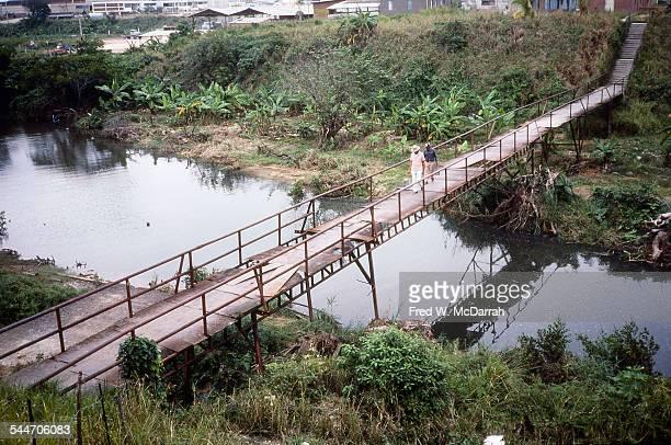 A pair of men carry metal buckets as they cross a rickety bridge at a sugar cane plantation off the Via Blanca near Varadero Cuba January 1983