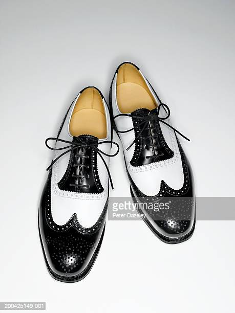 Pair of mens black and white classic brogue shoes, elevated view
