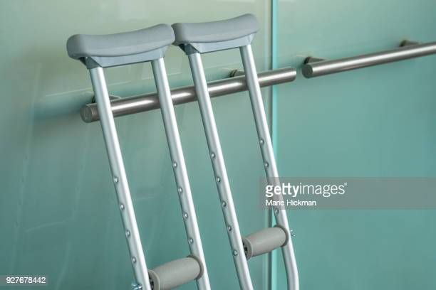 Pair of metal crutches leaning against a modern steel handle on a glass door.