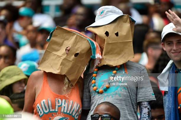 Pair of Miami Dolphins fans wear bags on their heads during the first half of the game against the Baltimore Ravens at Hard Rock Stadium on September...