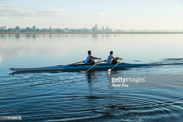 pair of mixed race rowers sculling on lake at dawn - dedication stock pictures, royalty-free photos & images