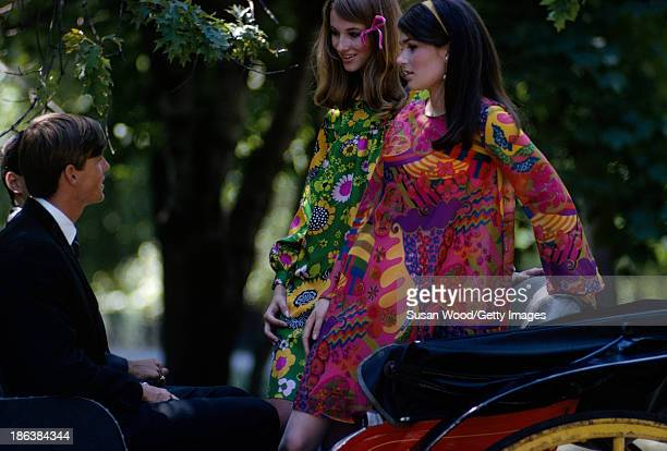 A pair of models one in a green floral print dress and the other in a red paisley print dress sit on a carriage in Central Park as they talk with a...