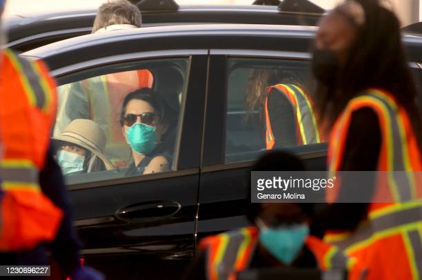 Pair of motorists wait for a COVID-19 vaccine as medical staff and workers give vaccines on the first day as California State University Northridge...