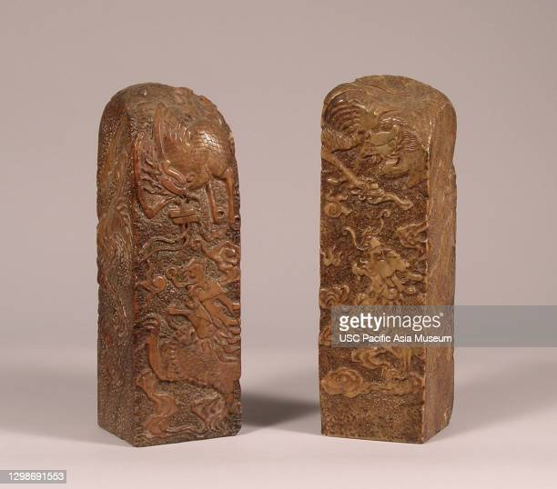 Pair of mottled brown soapstone seals with design of phoenix bird flying over a dragon chasing the flaming pearl, China, 19th Century, soapstone,...