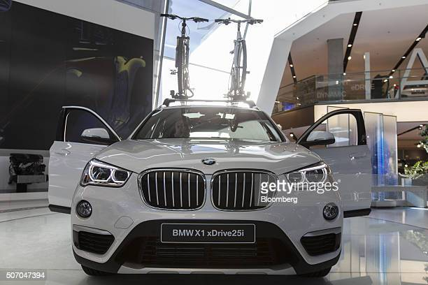 A pair of mountain bikes sit on the roof rack of a BMW X1 xDrive automobile produced by Bayerische Motoren Werke AG sits beside an electric charging...