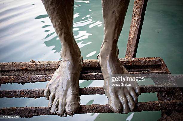 Pair of muddy feet standing on rusty bars on Chittagong beach where mega ships are being disassembled by laborers. Where do the mega freighters and...