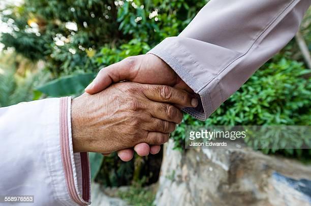 A pair of Muslim men wearing traditional dishdasha shake hands in greeting.