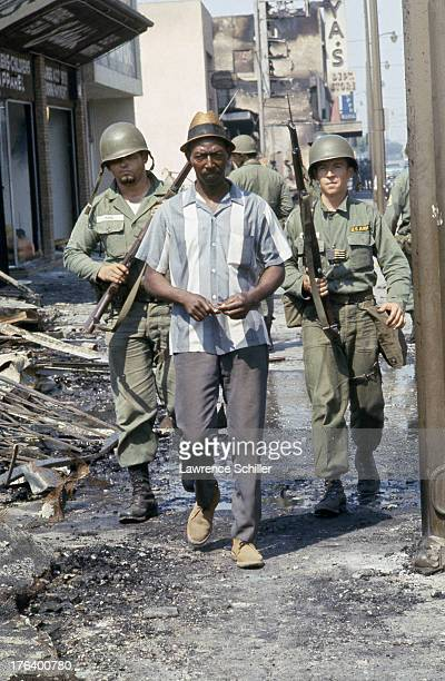 A pair of National Guardsmen escort an unidentified man past burnedout businesses and rubble in the Watts neighborhood after the declaration of...