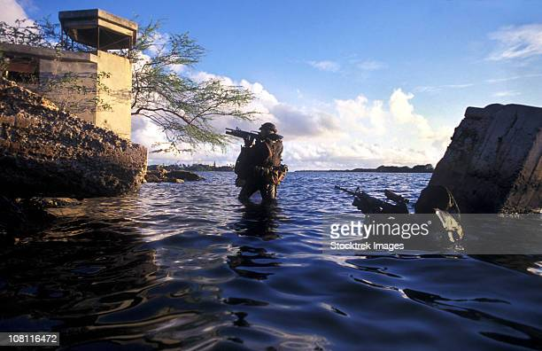 A pair of Navy SEAL combat swimmers transition from underwater to the surface.