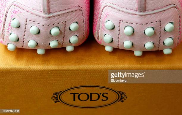 Pair of newly-manufactured Gommino leather moccasin loafers sit on a box following manufacture at Tod's SpA workshop in Sant'Elpidio a Mare, near...
