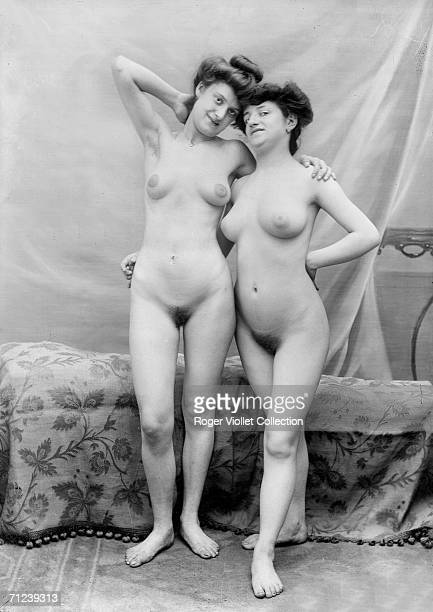 A pair of nude models pose together their arms around each other in front of a curtain France 1898