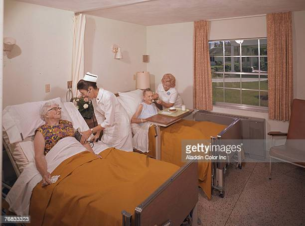 A pair of nurses work with two elderly women in a double occupancy room in an unidentified medical facility 1960s The nurse at right checks the blood...
