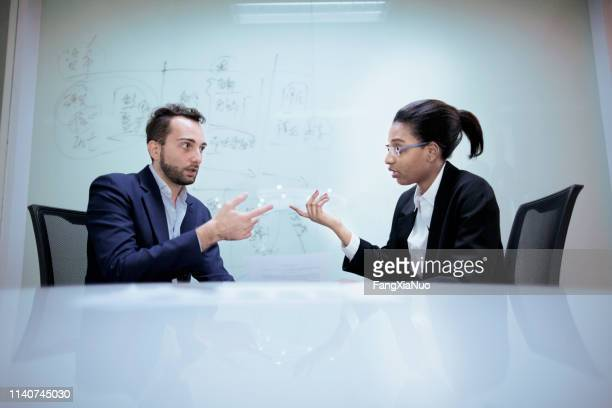 pair of office colleagues discussing future plans - debate stock pictures, royalty-free photos & images