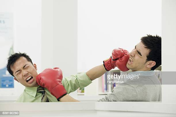 Pair of office coworkers fighting with boxing gloves in office
