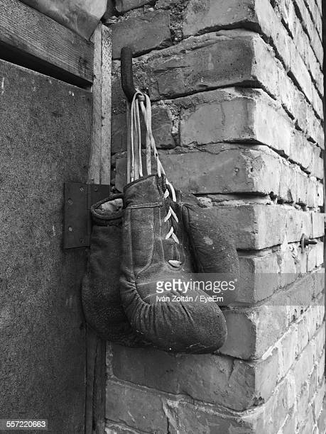 pair of old boxing gloves hanging on brick wall - iván zoltán stock pictures, royalty-free photos & images