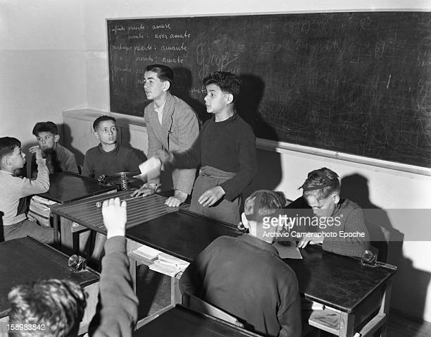 A pair of older students stand before a blackboard and lead a class assembly at a youth center Trieste Italy 1950
