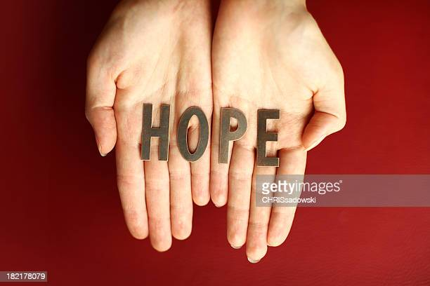 Pair of open hands on a red background holding the word HOPE