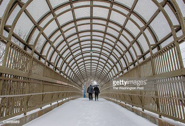 A pair of pedestrians make their way over the Forest Glen pedestrian bridge over a beltway ramp on yet another snowy morning on March 2014 in Silver...