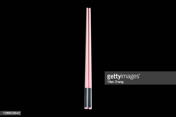 a pair of pink chopsticks with black background - changzhou stock pictures, royalty-free photos & images