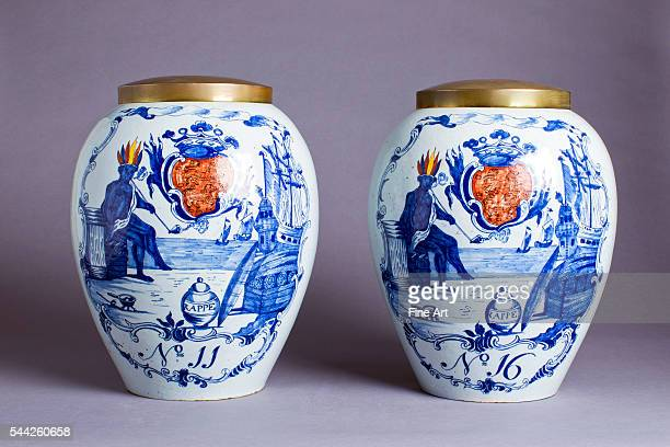 Pair of porcelain Delft blue and white tobacco jars made for the New York market showing a pipesmoking American Indian seated by New York harbor with...