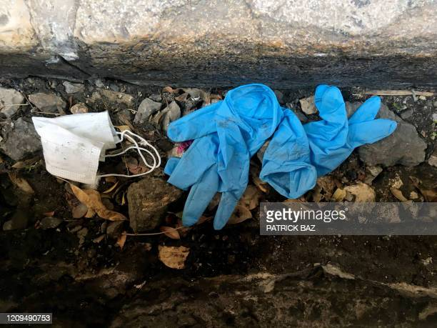 A pair of protective gloves and a mask are seen discarded on a sidewalk in the Lebanese capital Beirut on April 8 2020 Lebanon in midMarch ordered...