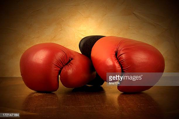 A pair of red boxing gloves on. Reflective brown surface