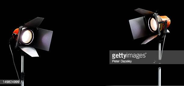 pair of red head film lights on black copy space - spotlight film stock photos and pictures