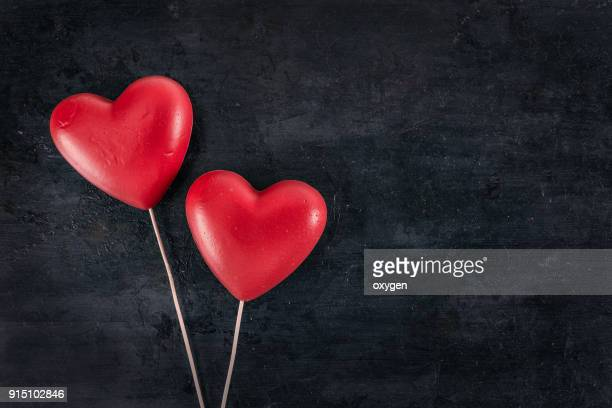 pair of red hearts on a black background - saint valentin photos et images de collection
