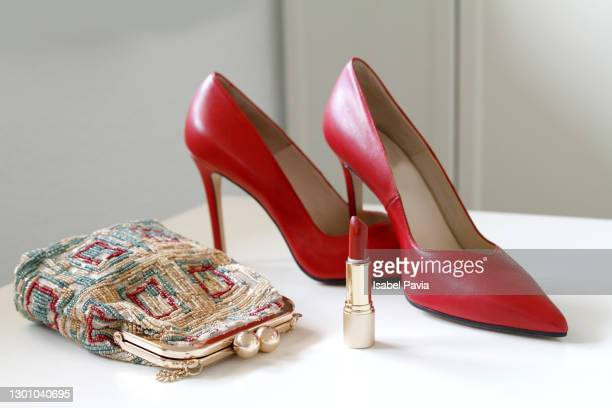 pair of red stilettos shoes, red lipstick and evening bag - gold purse stock pictures, royalty-free photos & images