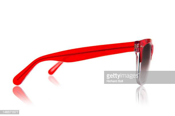 A pair of red sunglasses viewed from the side
